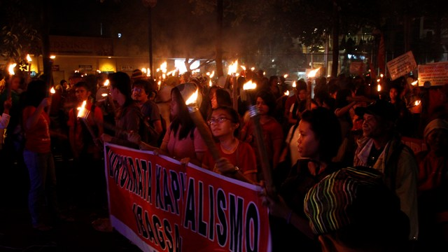 Protesters march to Rizal Park with torches.