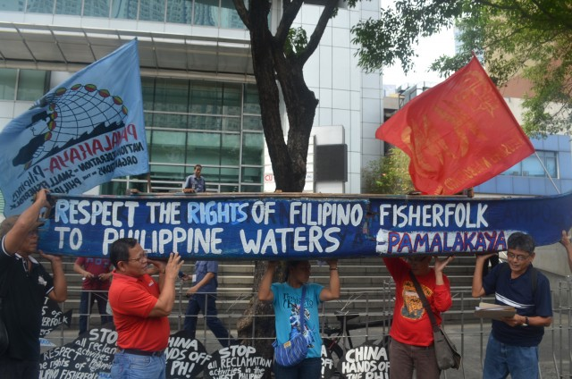 Anakpawis partylist Rep. Fernando Hicap (second from left) carries a symbolic fishing boat, with other fisher folk leaders, in a protest in front of the Chinese consulate in Makati (Photo by C. Cabanatan/Bulatlat.com)