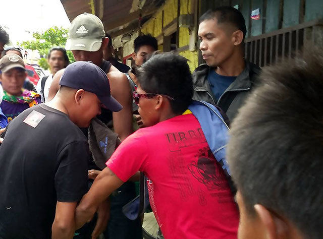 Army Private Ryan Alor (in blue cap, back to the camera) resisting apprehending marshals while Sgt. Rudy Ramoso (second from right wearing black jacket) looks on. (Photo by Karapatan Caraga)
