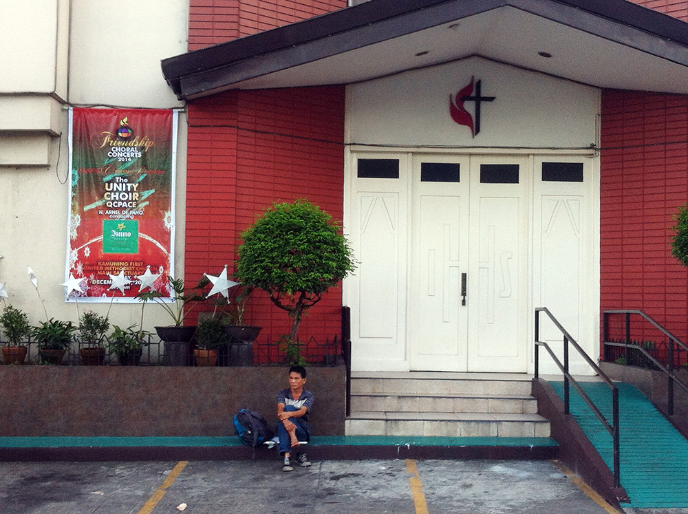 A man rests in front of a closed church building that appears to have already dispensed with Christmas celebrations. (Kamuning, Quezon City)