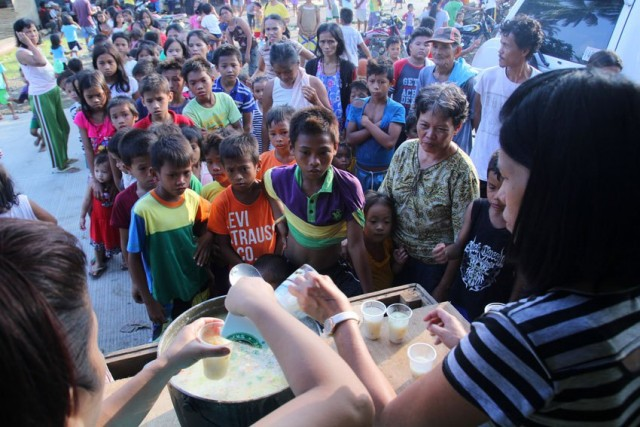 Evacuees line up for porridge prepared by church workers at the Marihatag municipal gym, in Surigao del Sur (Photo by A.Morandante/Davao Today)
