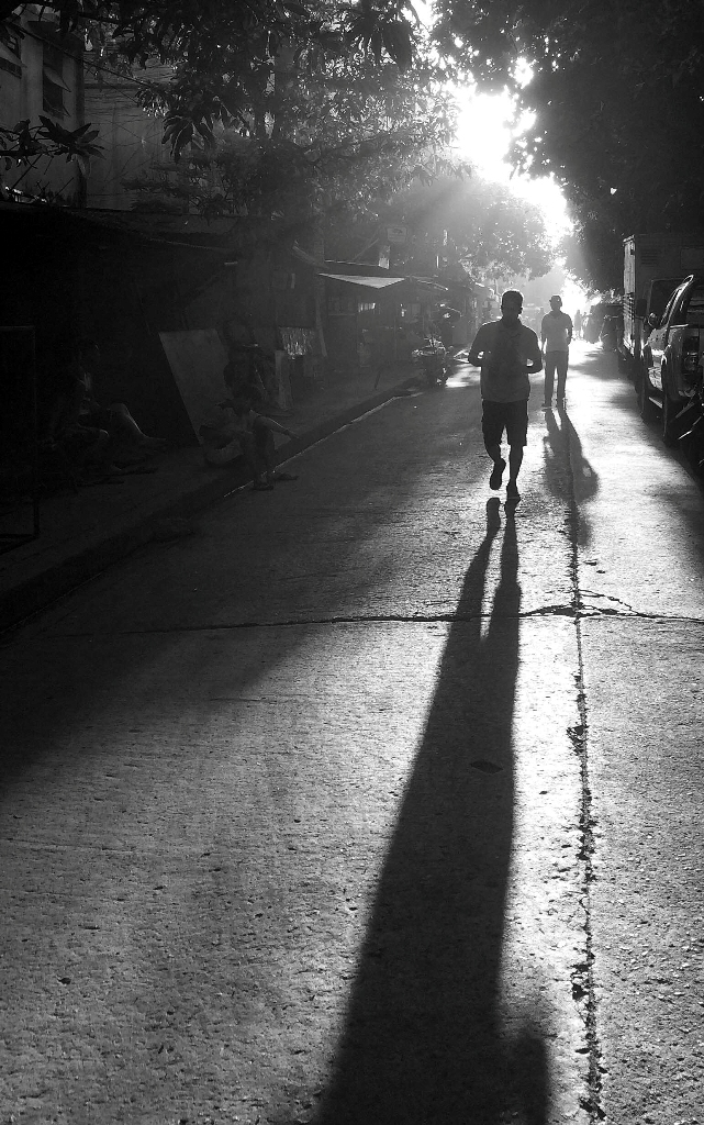 Early morning joggers cast long shadows as the newly-risen sun blesses their exertions. (Commonwealth, Quezon City)