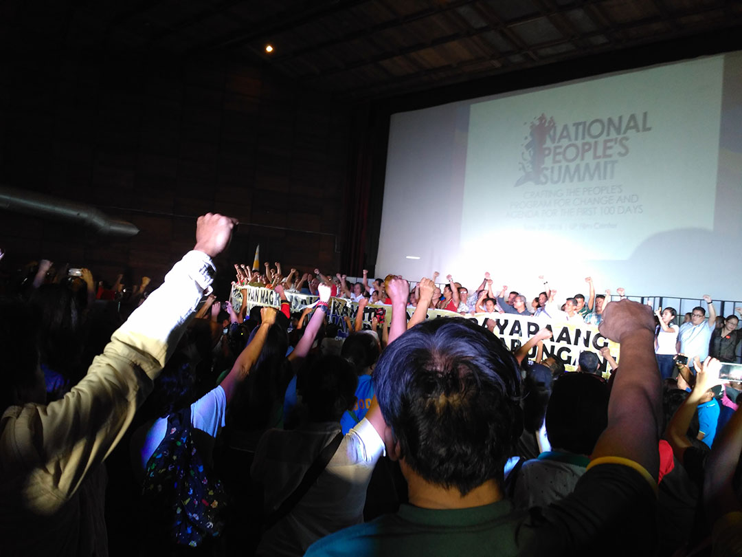 Participants of the National People's Summit raise their clenched fists as they vow to push for genuine change. (Photo by Ronalyn V. Olea)