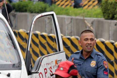 PO3 Franklin Kho, smirking as he got off the police mobile that plowed down and injured 30 protesters. (Photo by Pinoy Weekly)