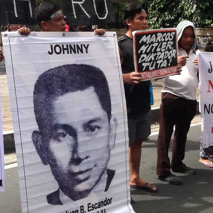 Protesting health workers at UP-PGH carry an image of Dr. Johnny Escandor, who joined the New People's Army and was abducted and killed, his briefs stuffed into his skull during martial law. (Photo by Dee Ayroso/Bulatlat)